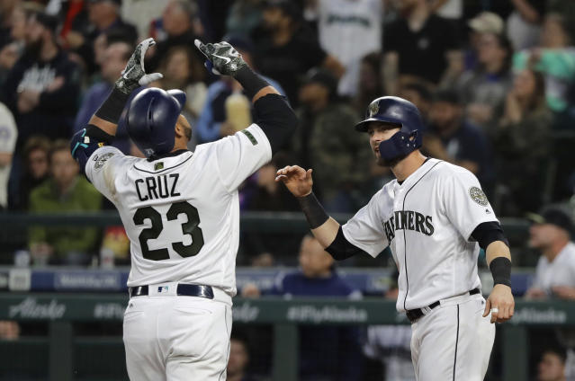 Seattle Mariners' Nelson Cruz (23) is greeted at the plate by Mitch Haniger, right, after Cruz hit a two-run home run to score Haniger during the sixth inning of the team's baseball game against the Minnesota Twins, Saturday, May 26, 2018, in Seattle. (AP Photo/Ted S. Warren)