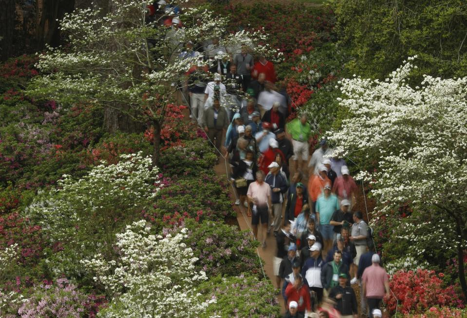 Fans walk along the sixth hole during a practice round for the Masters golf tournament Wednesday, April 4, 2018, in Augusta, Ga. (AP Photo/Charlie Riedel)