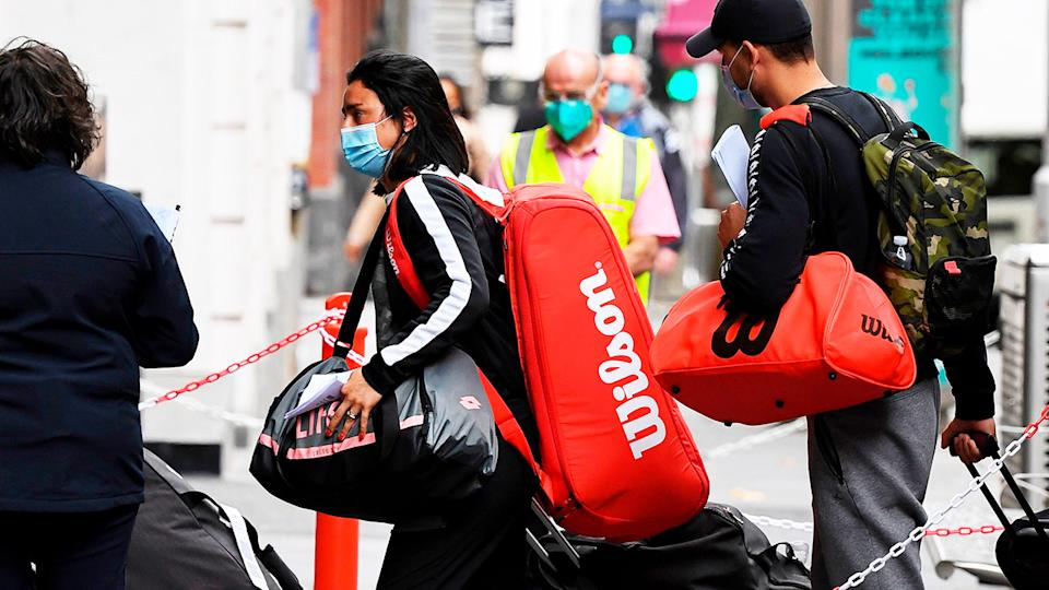 Tennis players wearing masks arrive in Melbourne from a flight ahead of the Australian Open.