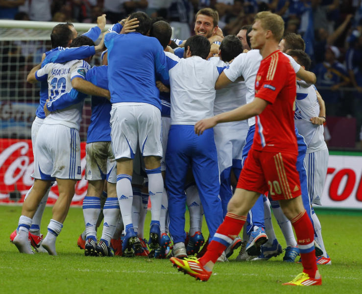 Greek players celebrate their 1-0 win as Russia's Pavel Pogrebnyak walks by at the end of the Euro 2012 soccer championship Group A match between Greece and Russia in Warsaw, Poland, Saturday, June 16, 2012. (AP Photo/Sergey Ponomarev)