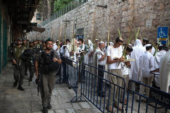 Israeli police stand guard as a group of Orthodox Jews pray in the Old City of Jerusalem during the Hoshana Rabbah prayers on the seventh day of the Jewish Sukkot holiday on October 4, 2015 (AFP Photo/Menahem Kahana)
