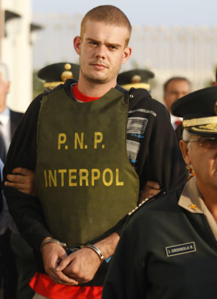 FILE - In this June 4, 2010, file photo, Dutch citizen Joran van der Sloot is escorted by police officers outside a Peruvian police station, near the border with Chile in Tacna, Peru. A Dutch newspaper said on Monday, Oct. 8, 2012, that Joran van der Sloot, who is serving a 28-year-sentence for murdering a young Peruvian woman, has impregnated a woman while imprisoned in Lima. (AP Photo/Karel Navarro, File)