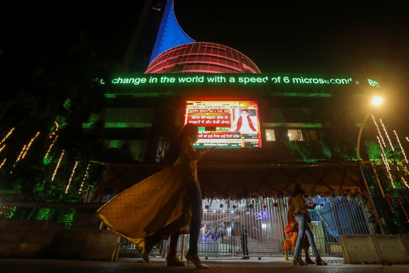 People walk past the Bombay Stock Exchange (BSE) building which was lit up during Diwali, the Hindu festival of lights, in Mumbai