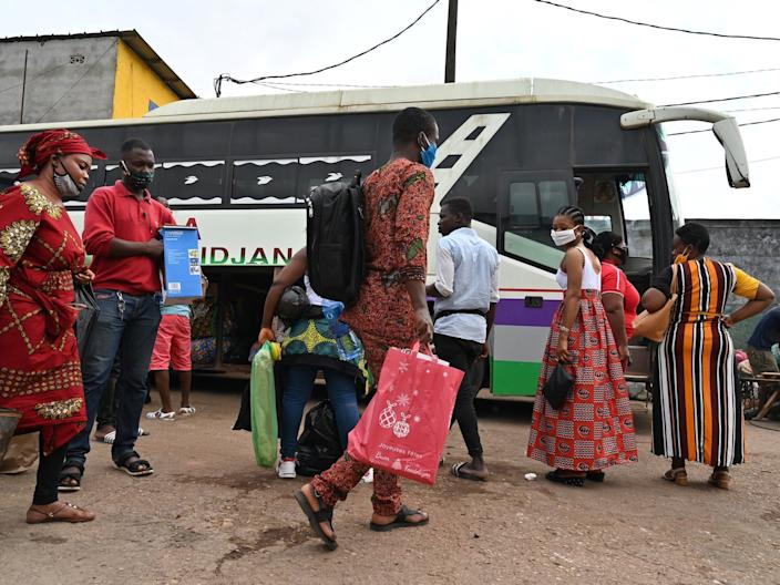 """Passengers wearing face masks prepare to board a bus at the Adjame bus station in Abidjan on July 15, 2020. <p class=""""copyright"""">ISSOUF SANOGO/AFP via Getty Images</p>"""