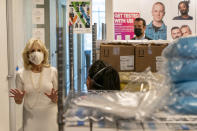 Beyond rows of personal protective medical equipment, first lady Jill Biden, left, speaks with Naseema Shafi, CEO of Whitman-Walker Health, during a tour of Whitman-Walker Health, Friday, Jan. 22, 2021, in Washington. (AP Photo/Jacquelyn Martin, Pool)