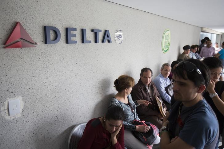 Customers wait their turn to be served in a line at the Delta airlines office in Caracas