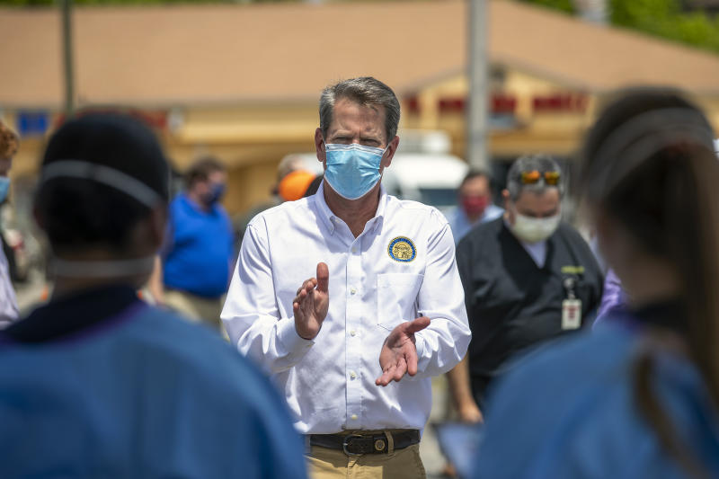 Georgia Governor Brian Kemp applauds healthcare workers for their service while touring a community COVID-19 testing site in the parking lot of La Flor de Jalisco #2 during a visit to Gainesville on May 15, 2020. (Alyssa Pointer/Atlanta Journal-Constitution via AP)