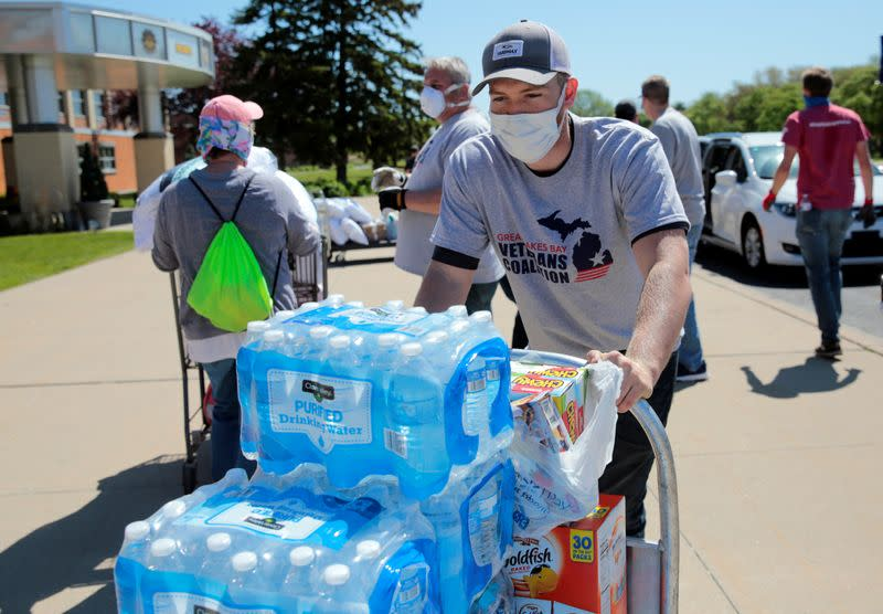 Volunteers unload water and supplies at a centre for residents evacuated from their homes along the Tittabawassee River, after several dams breached, in Midland