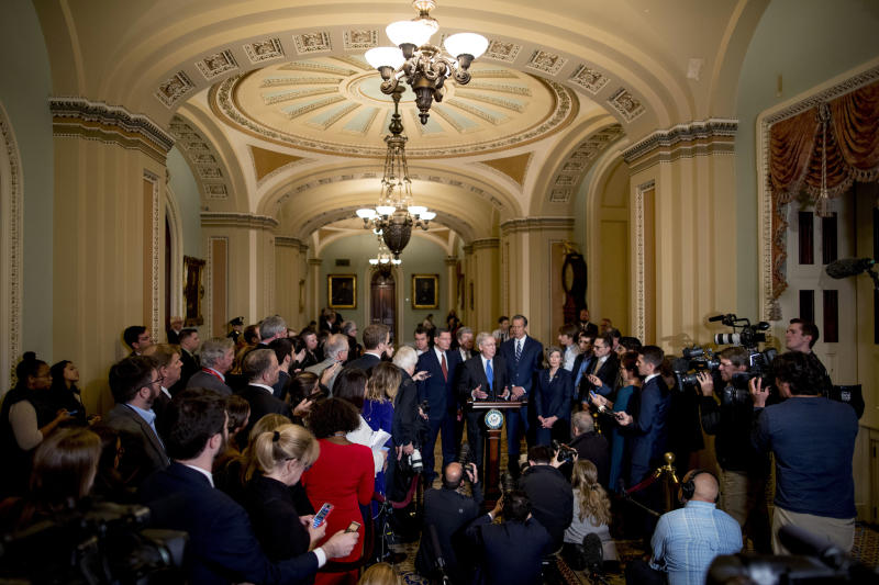 FILE - In this Tuesday, Dec. 10, 2019, file photo, Senate Majority Leader Mitch McConnell, R-Ky., accompanied by from left, Sen. Todd Young, R-Ind., Sen. John Barrasso, R-Wyo., Sen. Roy Blunt, R-Mo., Senate Majority Whip Sen. John Thune, R-S.D., and Sen. Joni Ernst, R-Iowa, speaks to reporters during a news conference, on Capitol Hill in Washington. Reporters at the Capitol want more cameras in the Senate to cover the impeachment trial and fewer restrictions to talk to senators when they are not sitting in judgment of the president. (AP Photo/Andrew Harnik, File)