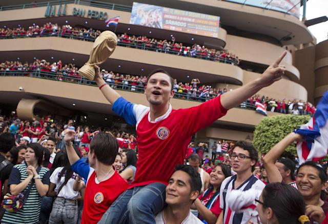 A Costa Rica soccer fan holds up a replica of the World Cup trophy as people celebrate Costa Rica's victory over Greece at a Brazil World Cup round of 16 game in San Jose, Costa Rica, Sunday, June 29, 2014. Costa Rica won a penalty shootout 5-3 after the match ended 1-1 following extra time. (AP Photo/Esteban Felix)