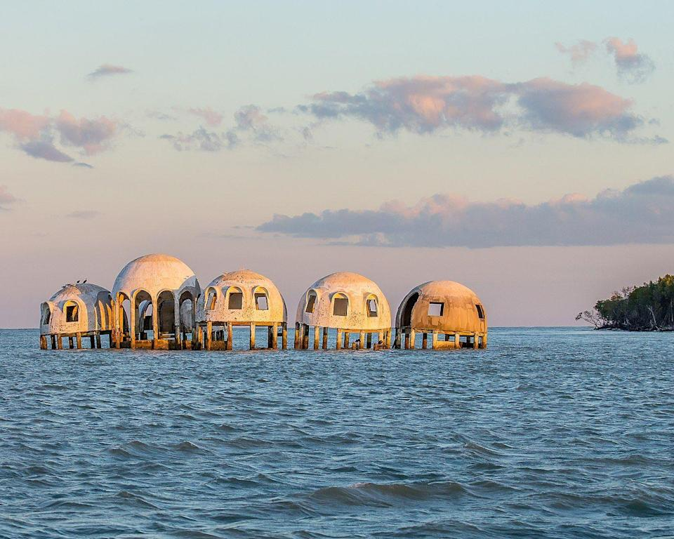 """<p><strong>Cape Romano Dome House - Cape Romano Island, FL</strong></p><p>Not far off of the shore of Cape Romano Island sits—er, floats—several dome structures built in the 1980s by the Lee family. The dome-home was occupied through the 1990s, but recent weather conditions and erosion have made the property inhabitable. Now, four of the six domes still remain, and they sit empty on the sea—making for a uniquely creepy visual.</p><p>Photo: Wikimedia Commons/<a href=""""https://en.wikipedia.org/wiki/Cape_Romano_Dome_House#/media/File:Slipping_into_the_Sea_(25278613801).jpg"""" rel=""""nofollow noopener"""" target=""""_blank"""" data-ylk=""""slk:Andy Morffew"""" class=""""link rapid-noclick-resp"""">Andy Morffew</a></p>"""
