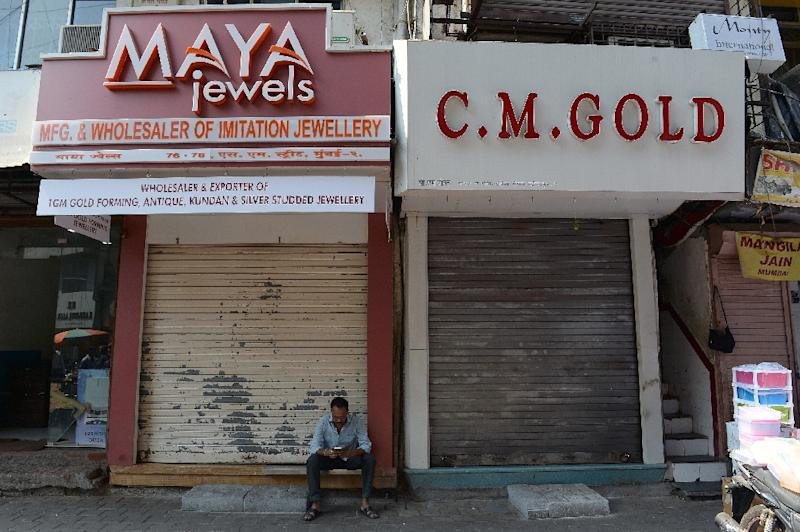 A man sits outside closed jewellery shops at Zaveri Bazar, the centre of India's jewellery trade, in Mumbai, on March 2, 2016 (AFP Photo/Indranil Mukherjee)