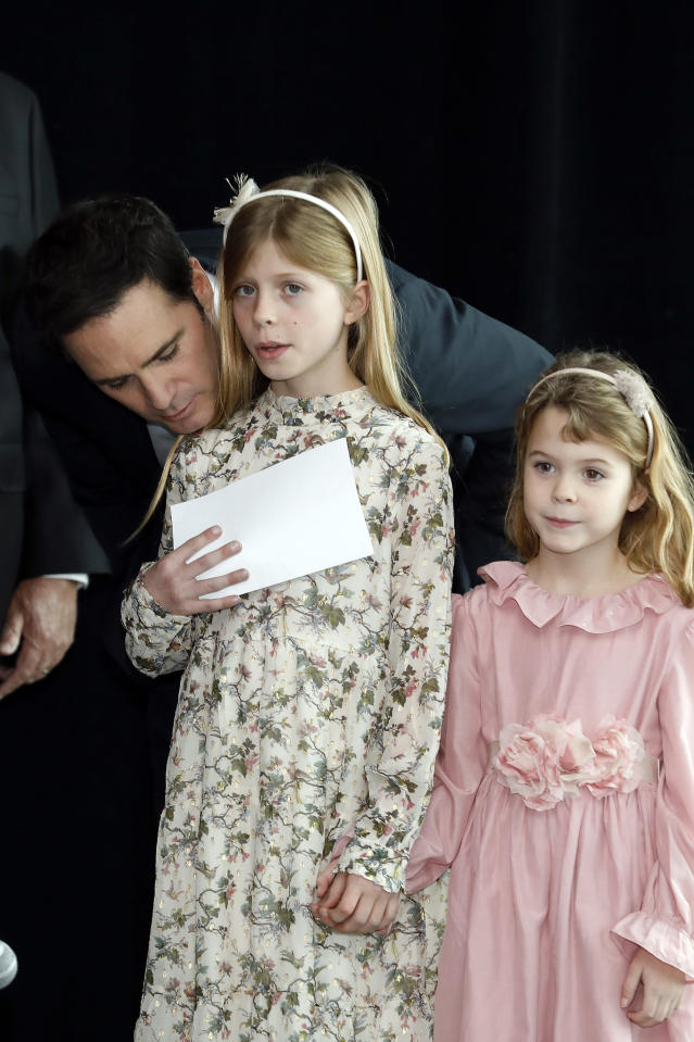 Jimmie Johnson has a word with his oldest daughter, Genevieve, as daughter Lydia waits to take the stage during his NASCAR retirement announcement at Hendrick Motorsports near Charlotte, N.C., Thursday, Nov. 21, 2019. (AP Photo/Bob Leverone)