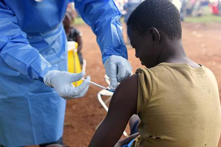 A Congolese health worker administers Ebola vaccine to a boy who had contact with an Ebola sufferer in the village of Mangina in North Kivu province of the Democratic Republic of Congo, August 18, 2018. REUTERS/Olivia Acland/Files