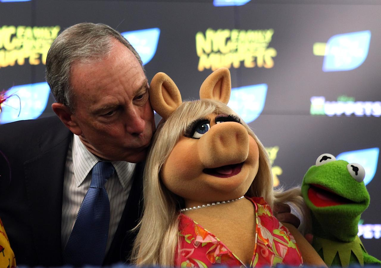 New York City Mayor Michael Bloomberg kisses Muppet Miss Piggy as Kermit the Frog looks on during a news conference on April 13, 2012 in New York City.  NYC Mayor Michael Bloomberg and NYC and Co. announced today that the Muppets will act as New York City's official family ambassadors for the next year. The Muppets will will encourage family travel to New York City by highlighting the best ways for families to experience the city.  (Photo by Justin Sullivan/Getty Images)