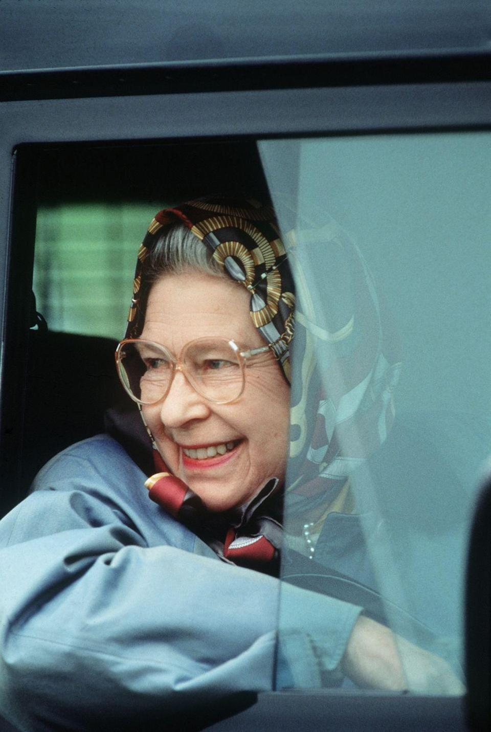 <p>Sporting a signature headscarf, the Queen was captured driving herself around Windsor.</p>