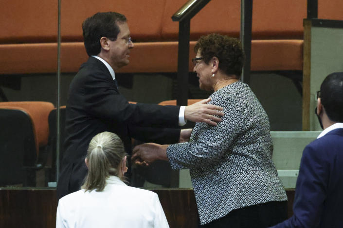Presidential candidates Isaac Herzog, left, and Miriam Peretz greet each other during a special session of the Knesset, whereby Israeli lawmakers elect a new president, at the plenum in the Knesset, Israel's parliament, in Jerusalem on Wednesday, June 2, 2021. (Ronen Zvulun/Pool Photo via AP)