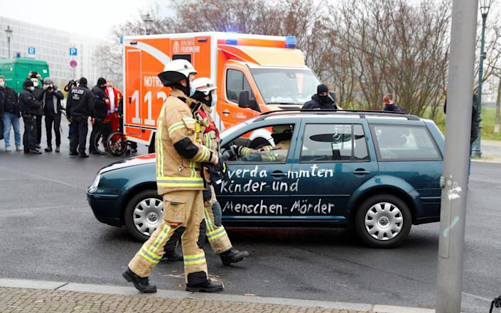 Firefighters remove the car that crashed into the gate - FABRIZIO BENSCH /REUTERS