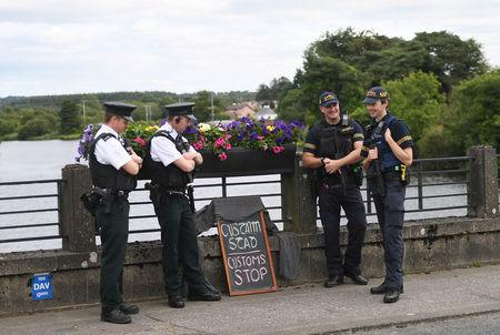 Officers of the Northern Ireland Police Service chat with colleagues from Ireland's Garda next to a sign left by tourists at the  borderline between Northern Ireland and Ireland in St Belleek, in Fermanagh, Northern Ireland, July 19, 2018. REUTERS/Clodagh Kilcoyne