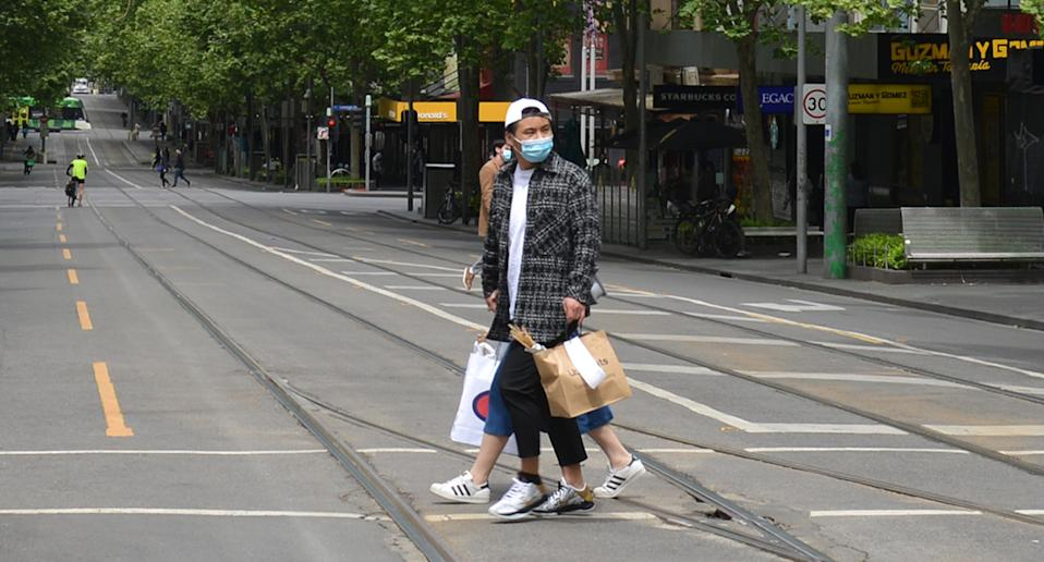 Two people in Melbourne walk along the street with face masks on.