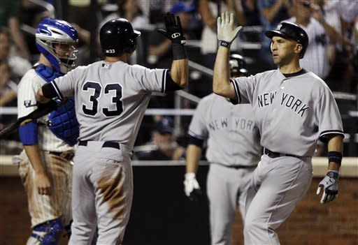 New York Yankees' Raul Ibanez, right, celebrates with teammate Nick Swisher (33) after hitting a three-run home run during the seventh inning of an interleague baseball game as New York Mets catcher Josh Thole looks on Saturday, June 23, 2012, in New York. (AP Photo/Frank Franklin II)