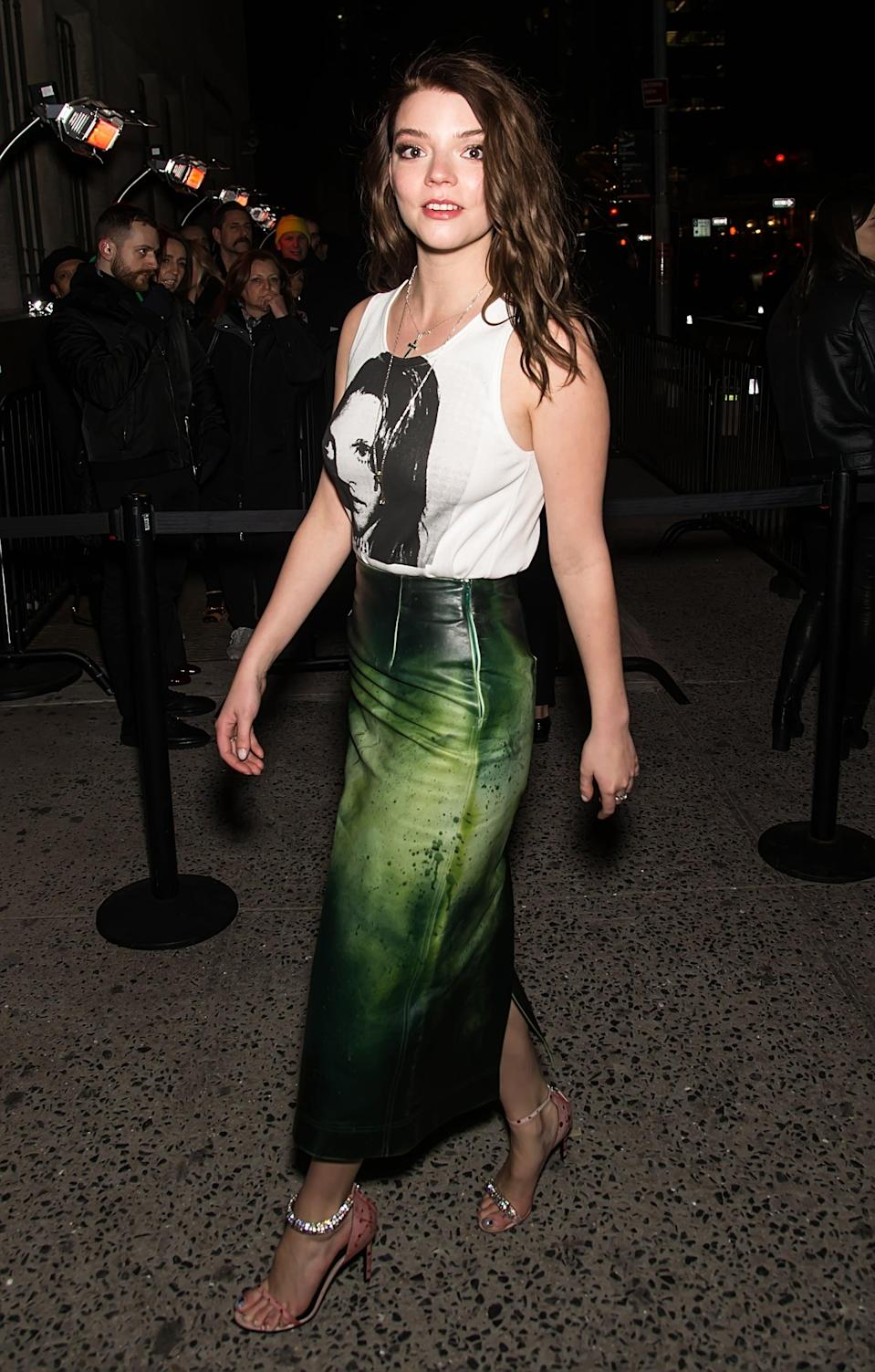 <p>Anya wore our idea of the perfect '90s rock concert look to the Calvin Klein show in New York City, breaking up her graphic muscle tee and crystal embellished sandals with a paint splash leather skirt.</p>