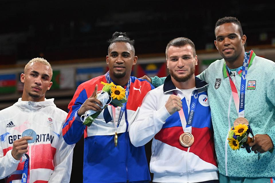 (LtoR) Silver medallist Britain's Benjamin Whittaker, gold medallist Cuba's Arlen Lopez, bronze medallists Russia's Imam Khataev and Azerbaijan's Loren Berto Alfonso Dominguez celebrate with their medal on the podium after the men's light heavy (75-81kg) boxing final bout during the Tokyo 2020 Olympic Games at the Kokugikan Arena in Tokyo on August 4, 2021. (Photo by Buda MENDES / POOL / AFP) (Photo by BUDA MENDES/POOL/AFP via Getty Images)