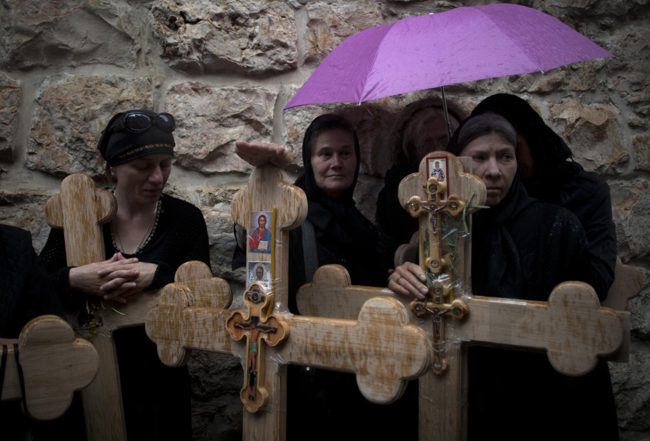 Christian pilgrims hold crosses on their way to the Church of the Holy Sepulcher, traditionally believed to be the site of the crucifixion and burial of Jesus Christ, during the Good Friday procession and the Way of the Cross, in Jerusalem's Old City, Friday, April 22, 2011. Christian pilgrims from around the world filled the narrow cobblestone streets of Jerusalem's Old City on Good Friday, some carrying large wooden crosses as they followed the route Jesus took on the way to his crucifixion.