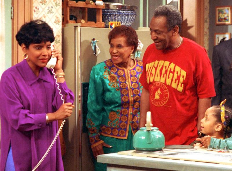 """FILE - In this 1992 file photo originally released by NBC, Phylicia Rashad, portraying Clair Huxtable, left, talks on the telephone while Clarice Taylor, portraying Anna Huxtable, center, and Bill Cosby, portraying Dr. Cliff Huxtable and Raven Symone portraying Olivia, right, look on in a scene from """"The Cosby Show."""" Why settle for one great mom when, as any TV viewer knows, you can adopt a series of them? AP Television Writer Lynn Elber chooses five of the best sit com moms, from the demure 1950s version to the freewheeling 21st-century incarnation. The character of Clair Huxtable remained a calm center of a whirlwind of activity, while tending to a legal career and caring for her five children and """"big kid"""" husband. (AP Photo/NBC, file)"""
