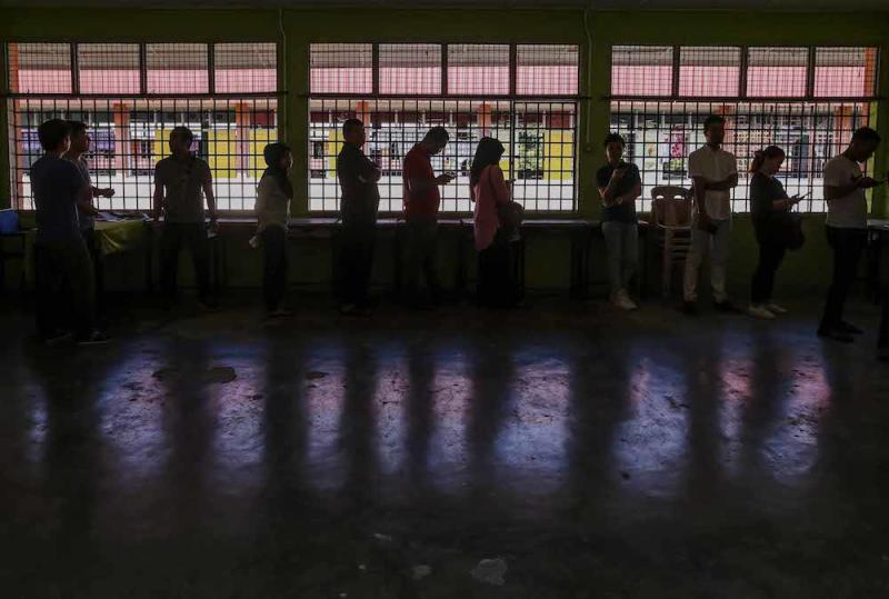 Voters queue to cast their votes outside a polling station during the 14th general elections in SMK Sri Muar, Muar May 9, 2018. — Picture by Firdaus Latif