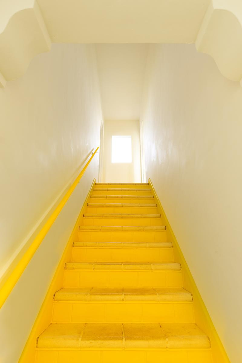 "The designer chose Benjamin Moore Bold Yellow for the home's interior stairwell. ""When the color reflects off the white walls, it makes the whole space glow,"" she says."