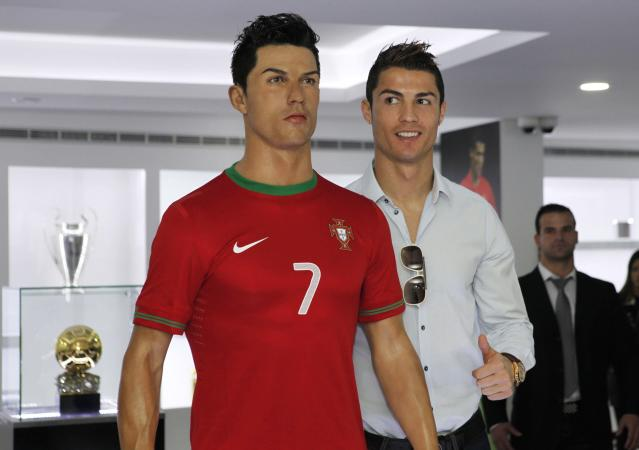 Cristiano Ronaldo, who plays for Real Madrid and Portugal's national soccer team, poses with his statue during the inauguration of his museum in Funchal December 15, 2013. Ronaldo opened a museum in his honour in his birthplace on Sunday, which he said had extra room for the Ballon d'Or and many other trophies to come. REUTERS/Duarte Sa (PORTUGAL - Tags: SPORT SOCCER)