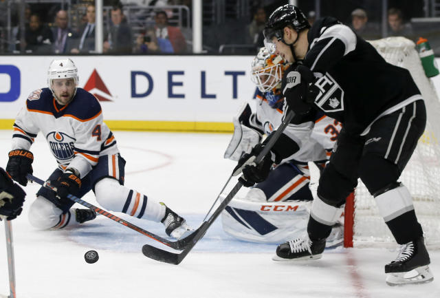Edmonton Oilers goaltender Cam Talbot, center, stops a shot by Los Angeles Kings right wing Dustin Brown, right, with defenseman Kris Russell, left, defending during the second period of an NHL hockey game in Los Angeles, Sunday, Nov. 25, 2018. (AP Photo/Alex Gallardo)