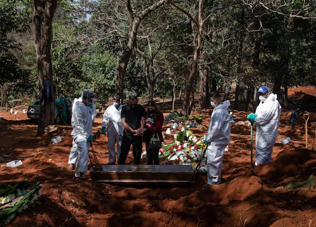 SAO PAULO, BRAZIL - MAY 18: Adenilson Souza Costa, 47 years, and his coworkers wearing protective gear show solemnity during a burial at Vila Formosa Cemetery amidst the coronavirus (COVID-19) pandemic on May 18, 2020 in Sao Paulo, Brazil. Adenilson Souza Costa is a gravedigger at Vila Formosa Cemetery for over 25 years. The Vila Formosa Cemetery is the largest in Latin America and compared to data from a year ago, the cemetery had an increase of 50% in number of burials. Because of the pandemic, over 15,000 new graves were opened and out of the 62 burials that took place on May 18, 2020, 32 were confirmed to be coronavirus (COVID-19) victims. According to the Brazilian Health Ministry, Brazil has over 260,000 positive cases of coronavirus (COVID-19) and more than 17,000 deaths. (Photo by Alexandre Schneider/Getty Images)