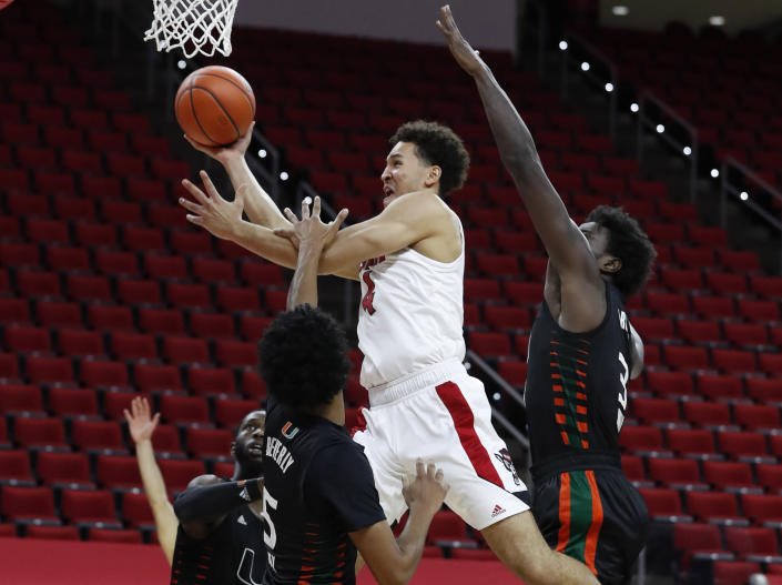 North Carolina State's Jericole Hellems (4) drives to the basket past Miami's Harlond Beverly (5) and Nysier Brooks (3) during the first half of an NCAA college basketball game at PNC Arena in Raleigh, N.C., Saturday, Jan. 9, 2021. (Ethan Hyman/The News & Observer via AP)