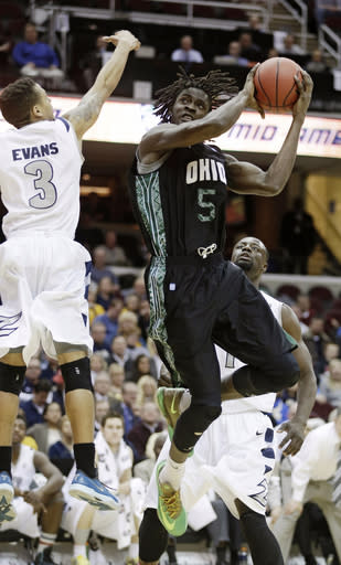 Ohio's Maurice Ndour (5) jumps to the basket against Akron's Nyles Evans (3) during the first half of an NCAA college basketball game at the Mid-American Conference tournament Thursday, March 13, 2014, in Cleveland. Akron defeated Ohio 83-77. (AP Photo/Tony Dejak)