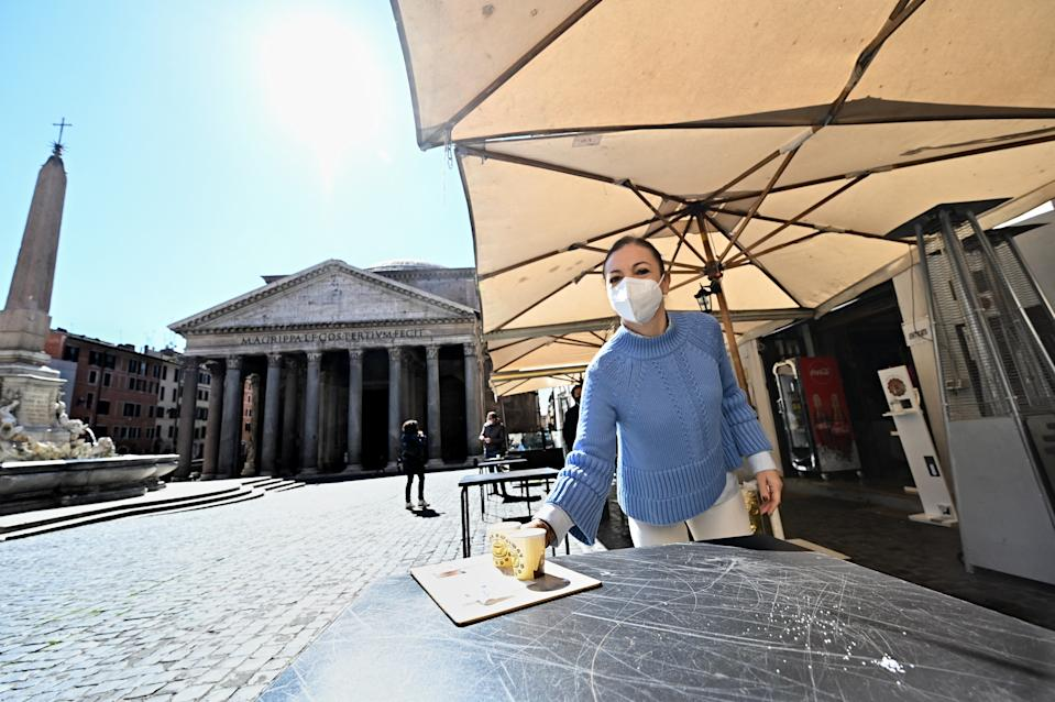 Staff of a coffe-restaurant, brings coffees for customers, in Piazza della Rotonda at the Pantheon, in central Rome, on March 15, 2021, as three-quarters of Italians entered a strict lockdown as the government put in place restrictive measures to fight the rise of COVID-19 infections. (Photo by Andreas SOLARO / AFP) (Photo by ANDREAS SOLARO/AFP via Getty Images)
