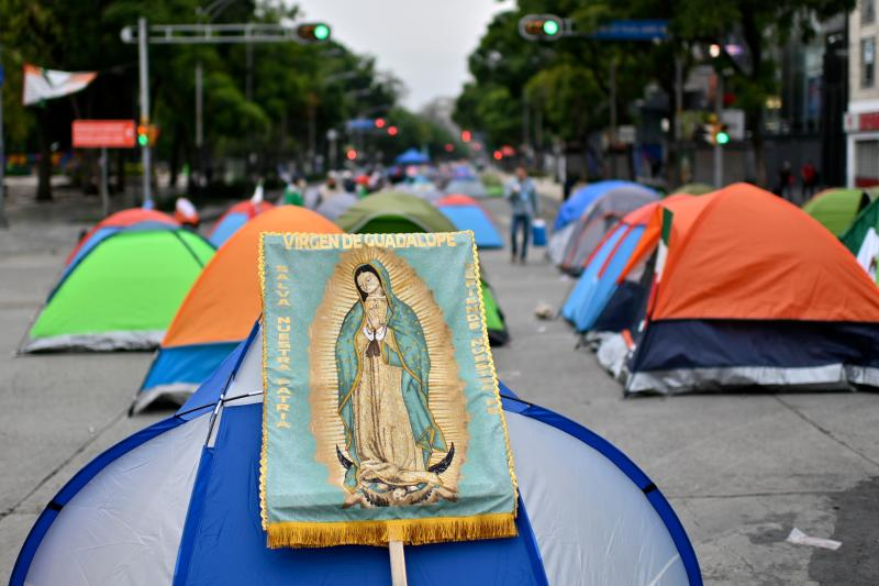 View of a banner depicting the Guadalupe virgin on a tent as members of the National Front Anti-AMLO (Frena), who will make a second attempt to reach Zocalo Square to protest against Mexican President Andres Manuel Lopez Obrador (ALMO), camp on Juarez street in Mexico City on September 20, 2020, a day after being prevented by the local police to get to the city's main square, amid the COVID-19 novel coronavirus pandemic. (Photo by PEDRO PARDO / AFP) (Photo by PEDRO PARDO/AFP via Getty Images)
