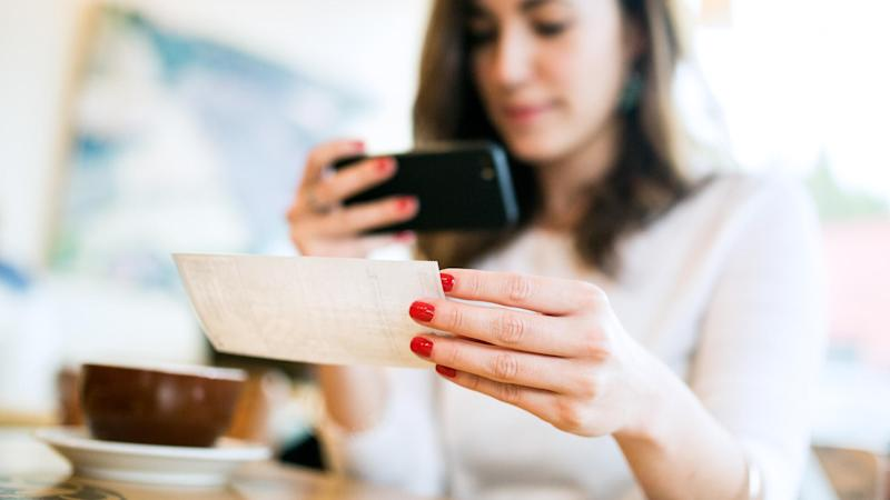 A smiling young woman takes a picture with her smart phone of a check or paycheck for digital electronic depositing, also known as