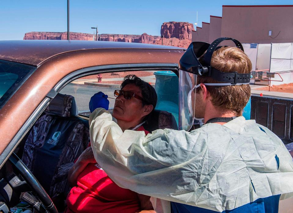 A nurse takes a swab sample from a Navajo Indian woman complaining of virus symptoms at a coronavirus testing center at the Navajo Nation town of Monument Valley in Arizona. Weeks of delays in delivering vital coronavirus aid to Native American tribes exacerbated the outbreak.