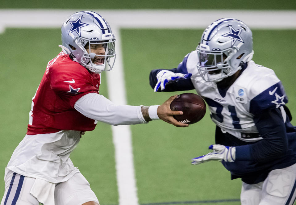 Dallas Cowboys quarterback Dak Prescott, left, hands the ball off to running back Ezekiel Elliott during an NFL football training camp practice at The Star, Friday, Aug. 28, 2020, in Frisco, Texas. (AP Photo/Brandon Wade)