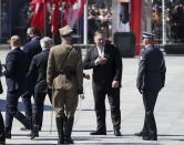 U.S. Secretary of State Mike Pompeo gestures toward Polish soldiers during ceremonies marking the centennial of the Battle of Warsaw, a Polish military victory in 2020 that stopped the Russian Bolshevik march toward the west, in Warsaw, Poland, Saturday Aug. 15, 2020. Pompeo attended as he wrapped up a visit to central Europe.(AP Photo/Czarek Sokolowski)