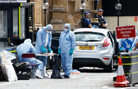 Forensic investigators work at the site after a car crashed outside the Houses of Parliament in Westminster, London