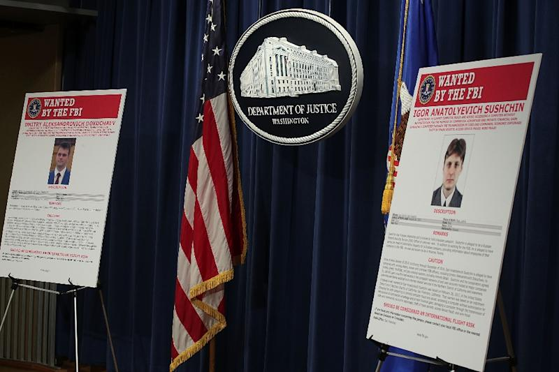 Wanted posters of Russian national and residents Igor Anatolyevich Sushchin (R) and Dmitry Aleksandrovich Dokuchaev (L) on display at a March 2017 Justice Department news conference on the Yahoo hack