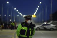 Police officer stands at a roadblock at a bridge crossing the Yangtze River to Hubei province in Jiujiang