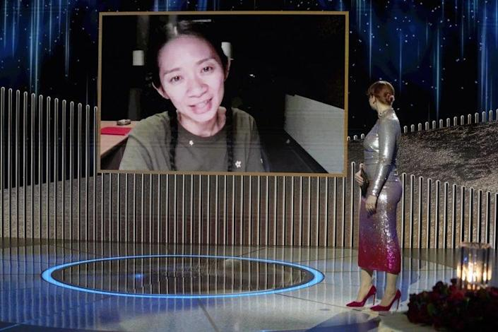78th ANNUAL GOLDEN GLOBE AWARDS -- Pictured: (l-r) Chloe Zhao accepts the Best Director - Motion Picture award for 'Nomadland' via video; Bryce Dallas Howard onstage at the 78th Annual Golden Globe Awards held at the Rainbow Room on February 28, 2021 -- (Photo by: Peter Kramer/NBC)