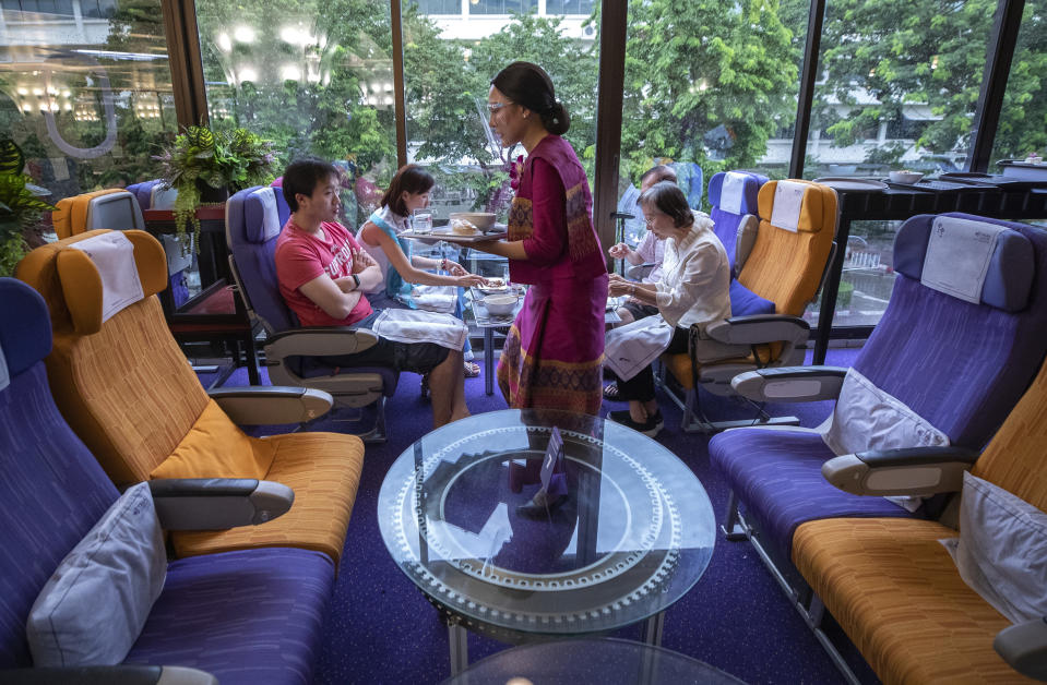 A flight attendant serves meals in a flight-themed restaurant at the Thai Airways head office in Bangkok, Thailand on Oct. 3, 2020. The airline is selling time on its flight simulators to wannabe pilots while its catering division is serving meals in a flight-themed restaurant complete with airline seats and attentive cabin crew. The airline is trying to boost staff morale, polish its image and bring in a few pennies, even as it juggles preparing to resume international flights while devising a business reorganization plan. (AP Photo/Sakchai Lalit)