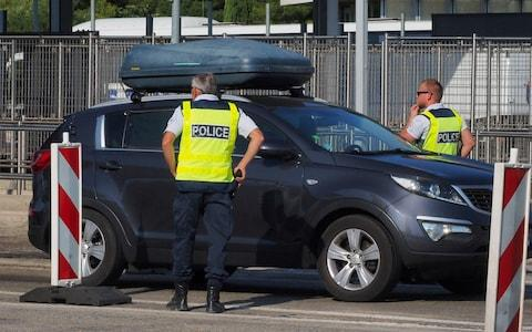 French police officers control vehicles coming across the border from Spain  - Credit: RAYMOND ROIG/AFP