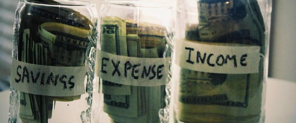 Jars of cash with Savings, Expense and Income written on them.