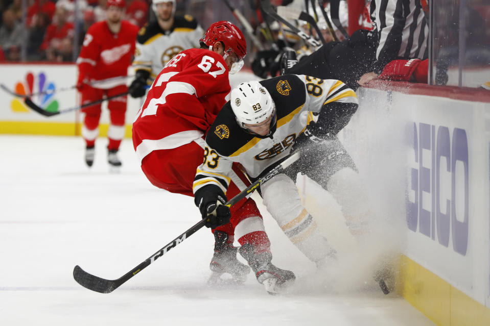 Detroit Red Wings left wing Taro Hirose (67) and Boston Bruins center Karson Kuhlman (83) battle for the puck in the second period of an NHL hockey game Sunday, Feb. 9, 2020, in Detroit. (AP Photo/Paul Sancya)